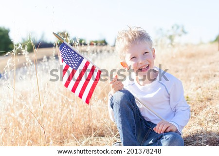 little boy holding american flag and celebrating 4th of July - stock photo