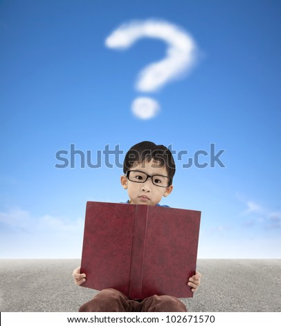little boy holding book and question mark cloud background - stock photo