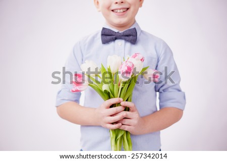 Little boy holding bunch of tulips - stock photo