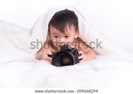 Little Boy holding camera and taking photo lying on bed - stock photo