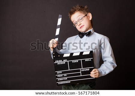 Little boy holding clapper board in hands. Cinema concept.