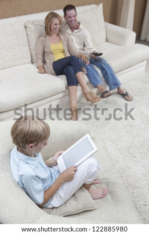 Little boy holding digital tablet with his parents watching TV at home - stock photo