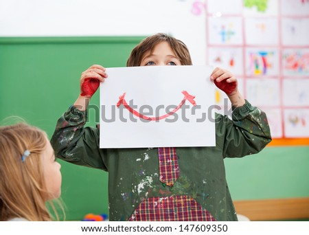 Little boy holding drawing paper on face while looking away in art class - stock photo