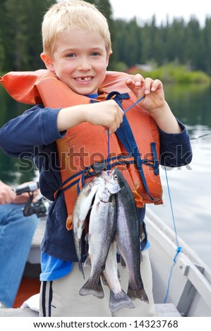 Little boy holding four trout with a big toothless smile