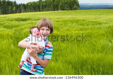 Little boy holding his newborn sister