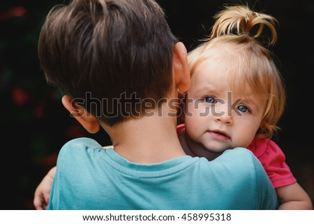 Little boy holding his sister. - stock photo