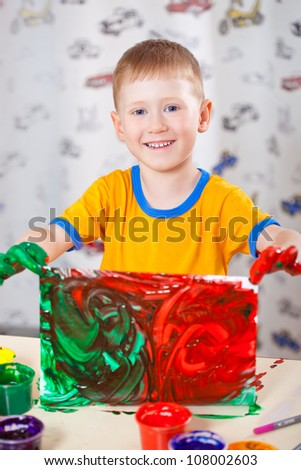 little boy holding painted picture with fingerpaints
