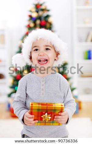 Little boy holding present in front of Christmas tree - stock photo