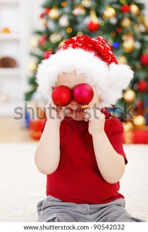 Little boy holding red Christmas decoration in front of eyes - stock photo