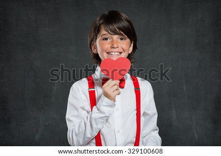 Little boy holding red heart. Portrait of lovable child smiling and looking at camera. Cute boy holding red heart isolated on blackboard with copyspace.  - stock photo