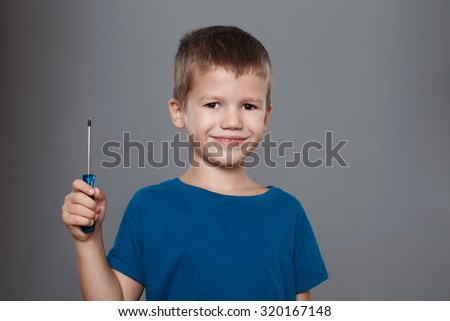 Little boy holding screwdriver on grey background