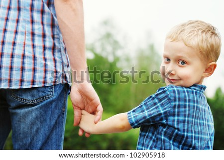 Little boy holding the hand of his father - stock photo