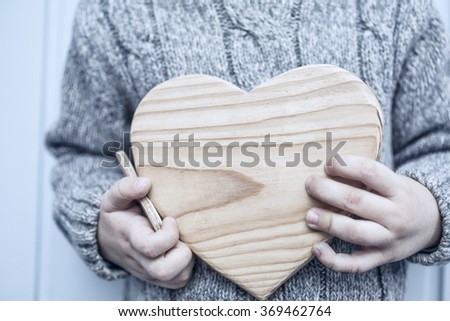 little boy holding two wood hearts - stock photo