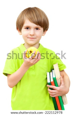 little boy holds a stack of books and an Apple - stock photo