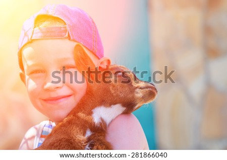 Little boy holds a young goat and smiling. Natural composition
