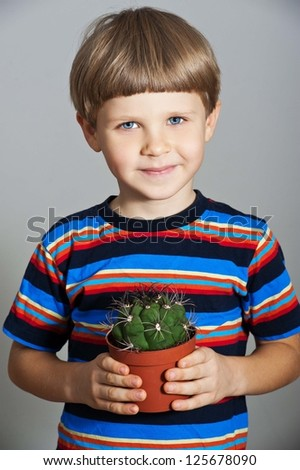 little boy holds his houseplant cactus