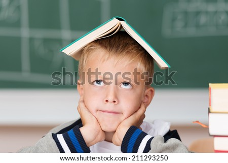 Little boy hoping to absorb knowledge sitting in class with his text book balanced on his head looking up with a rueful smile - stock photo