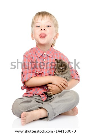 little boy hugging a kitten showing his tongue. isolated on white background