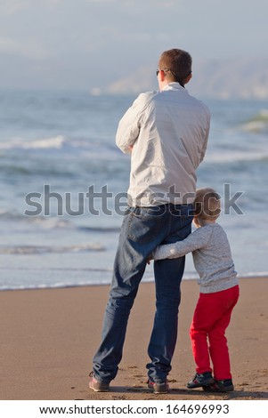 little boy hugging his father at the beach