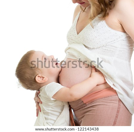 Little boy hugging pregnant mother's belly and looking up - stock photo