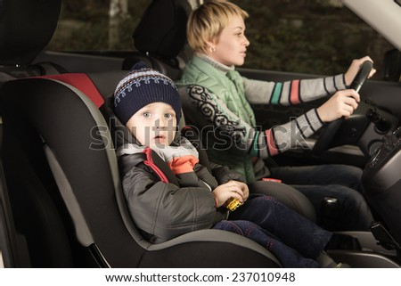 little boy in a a car seat, family in the car - stock photo