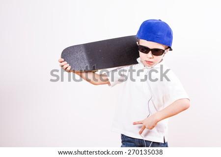 Little boy in a baseball cap listens to music - stock photo