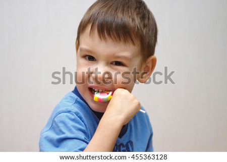 Little boy in a blue shirt eating lollipop and trying to bite his teeth candy