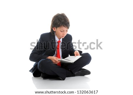little boy in a business suit reading a book sitting on the floor. Isolated on white background