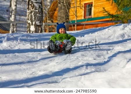 Little boy in a green jacket sledding in winter frost