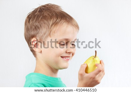 Little boy in a green shirt with a juicy yellow pear - stock photo