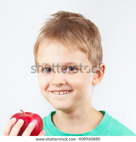 Little boy in a green shirt with ripe red apple