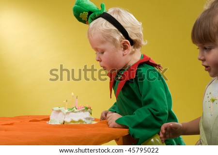 little boy in a green suit sitting at a table eating cake beside it is a beautiful girl in a pink dress - stock photo