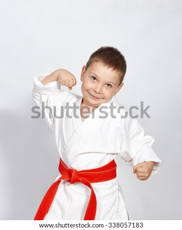 Little boy in a kimono with a red belt and shows his strength