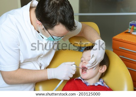 little boy in a red sweater went to the dentist in the dental chair sits next to a doctor to do the dentist to see if his teeth were okay/little boy in a red sweater went to the dentist - stock photo