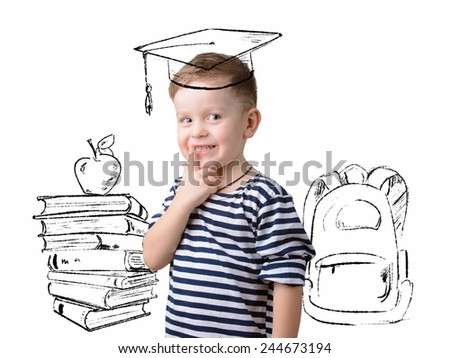 little boy in a square academic cap. Books, apple and backpack - stock photo