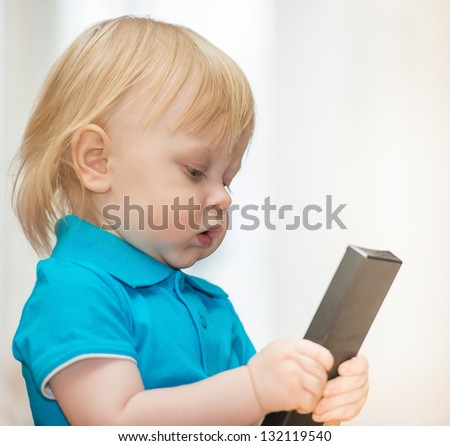 little boy in a turquoise shirt with the remote control for the TV - stock photo