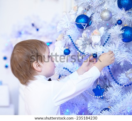 little boy in a white shirt and bow tie decorates a Christmas tree - stock photo