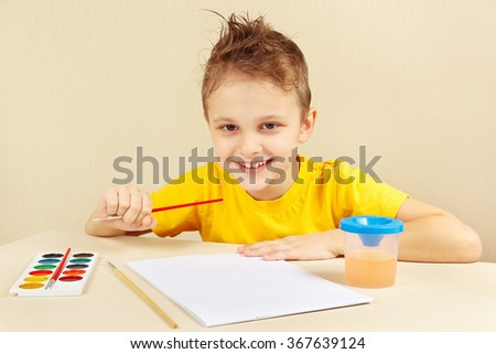 Little boy in a yellow shirt going to paint colors - stock photo