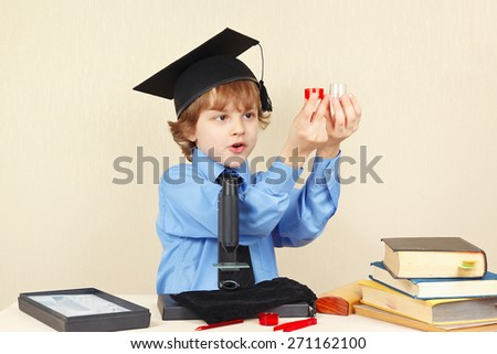 Little boy in academic hat conducts scientific research with the microscope - stock photo