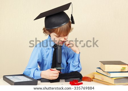 Little boy in academic hat funny thought, seeing something in a microscope  - stock photo