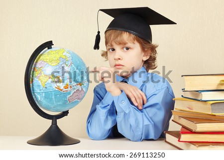 Little boy in academic hat showing on the globe among the old books - stock photo