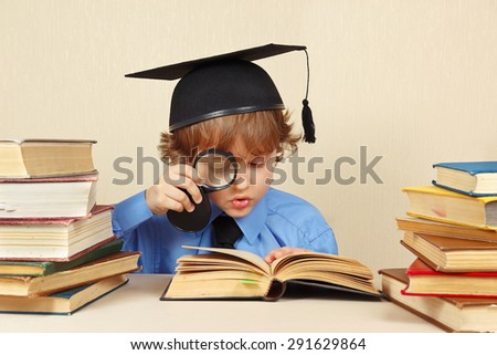 Little boy in academic hat studies an old books with a magnifier - stock photo