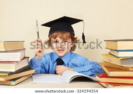 Little boy in academic hat with rarity pen among the old books - stock photo