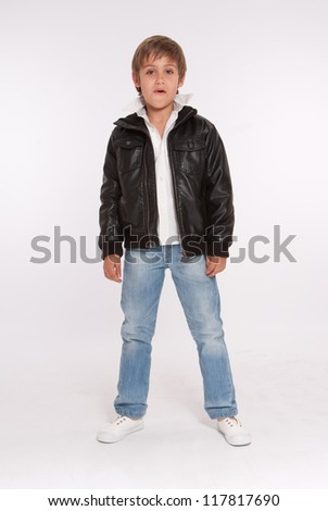 Little boy in blue jeans and a leather jacket - stock photo