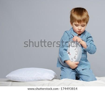 Little boy in blue pyjamas with clock  - stock photo