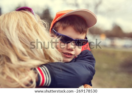 Little boy in cap and glasses embrace mother, Mother's day - stock photo