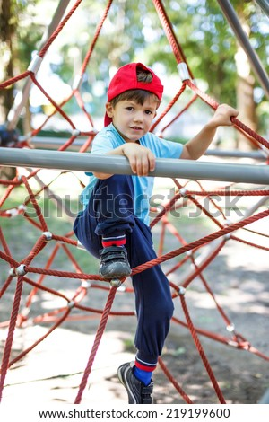 Little boy in cap climb on jungle gym at park - stock photo