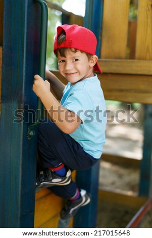 Little boy in cap climb up on jungle gym - stock photo