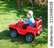 Little boy in cap drive electrical vehicle in garden, outdoor portrait - stock photo