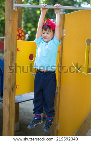 Little boy in cap hanging at playground, outdoor portrait - stock photo